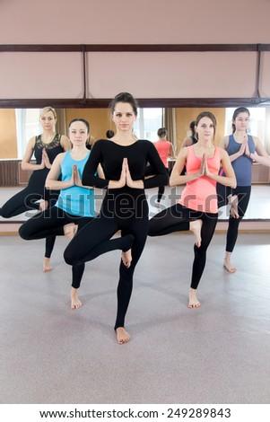 Sporty yogi girls in class in Yoga pose vrikshasana (Vriksasana or Tree Pose) using Namaste (full length) - stock photo