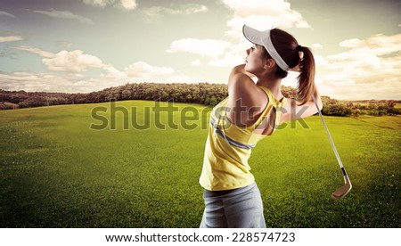 Sporty young female playing golf on the nature. Active girl in sportswear golfing in green field. - stock photo
