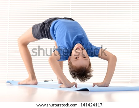 sporty young guy in a blue shirt on a light background - stock photo