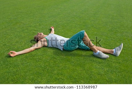 Sporty young man laying on green training field with his arms spread, relaxing. - stock photo
