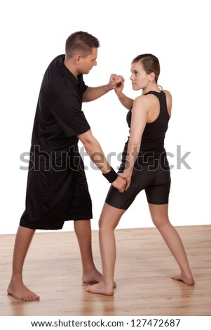Sporty young man practicing fighting sport with a young woman - stock photo