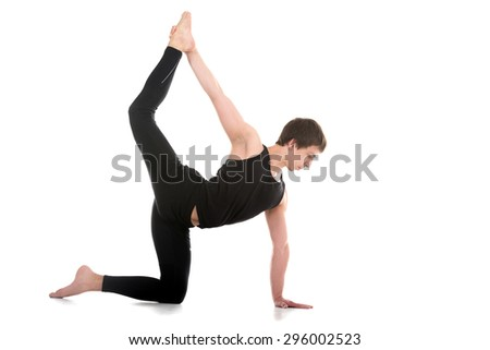 Sporty young man working out, yoga, pilates, fitness training, doing Royal Sunbird exercise, Chakravakasana, balancing cat-caw easy variation (one side hand and leg), full length - stock photo