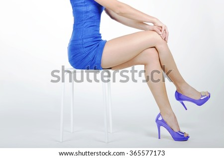 Sporty young woman body with a blue dress and blue high heels shoes sitting on a chair and crossed her legs, isolated on white background. - stock photo