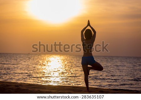 Sporty young woman exercising at seashore in warm summer sunlight, standing in asana Vrikshasana (Tree Pose), hands above the head in mudra, back view - stock photo