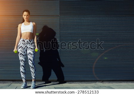 Sporty young woman holding weights standing on black wall background at sunset,attractive female taking break while working on her arms outdoors with copy space for your text message by side,flare sun - stock photo