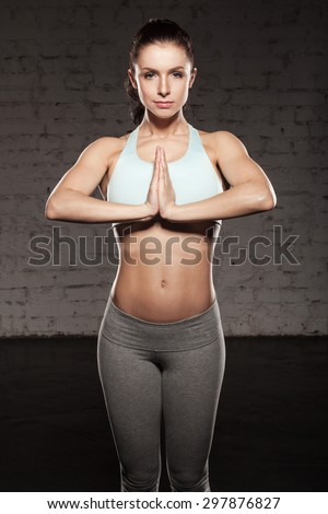 Sporty young woman in Namaste position at a fitness studio, fitness girl with muscular body, do her workout - stock photo