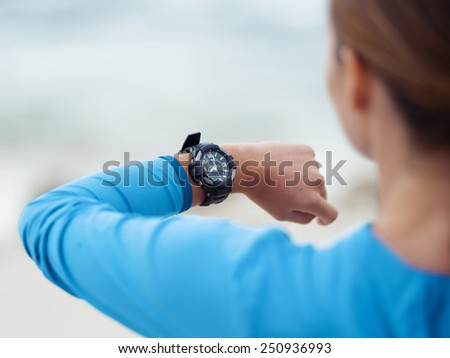 Sporty young woman looking at her watches - stock photo