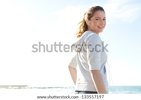 Sporty young woman on a beach taking a break from exercising and listening to music with her head phones, turning and smiling at camera against a blue sky. - stock photo