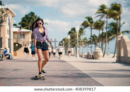Sporty young woman riding long board on Hollywood beach in Miami, florida. Filtered image. - stock photo