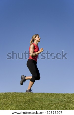 Sporty young woman running on the nature - stock photo