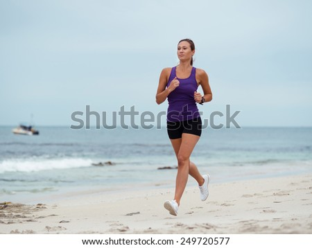 Sporty young woman running on the sea coast - stock photo