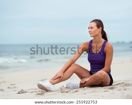 Sporty young woman stretching on the sea coast - stock photo