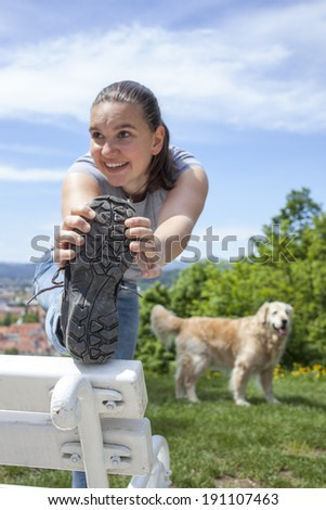 Sporty young woman stretching outdoor on park bench, Close-up, selective focus on on sport shoe sole - stock photo