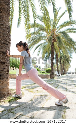 Sporty young woman training and stretching her legs in a park avenue with aligned palm trees during a sunny summer day while listening to music on her headphones, outdoors. - stock photo
