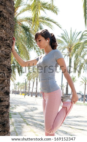 Sporty young woman training and stretching her legs on a stone pavement avenue with aligned palm trees during a sunny summer day while listening to music on her headphones, outdoors. - stock photo