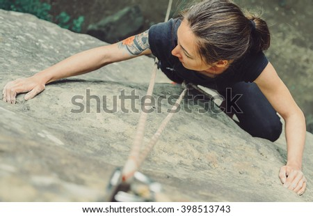 Sporty young woman wearing in safety equipment with rope climbing on stone rock in summer outdoor, top view - stock photo