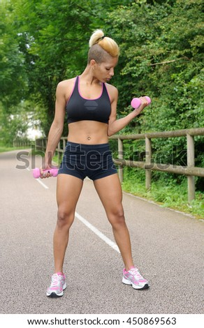 Sporty young woman with dumbbells - stock photo