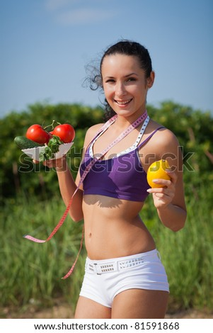 Sporty young woman with measuring tape and vegetables. Outdoors. Concept of healthy lifestyle. - stock photo