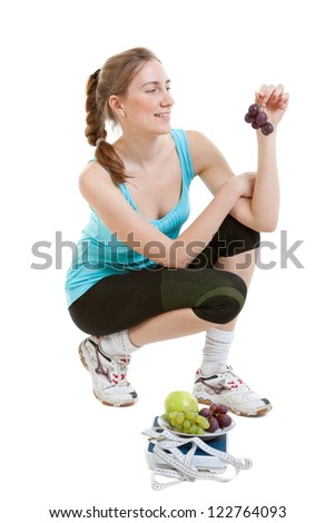 Sporty young woman with scales and fruits on a white background. Concept of healthy lifestyle - stock photo