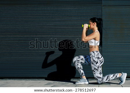 Sporty young woman working out with dumbbells while standing against black background outdoors, athletic female in workout gear doing weight training against wall with copy space for your text message - stock photo