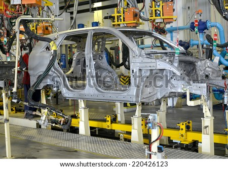 Spot contact welding of bodies of cars at automobile plant - stock photo