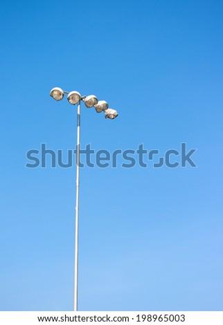 Spot light tower in blue sky - stock photo