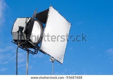 Spotlight on blue sky background - stock photo