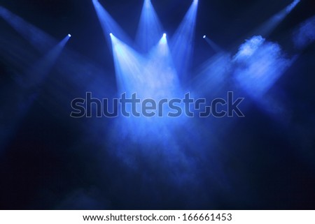 spotlights that illuminate the stage at a concert with fog - stock photo