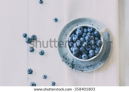 Spotted blue ceramic cup of blueberries with saucer at white textile napkin over wooden table. Rustic style. Top view. Natural day light with retro filter effect. - stock photo