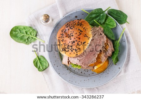 Spotted plate with Homemade sandwich with baked meat and soft-boiled egg, spinach salad and salt over white wooden table with white textile. Top view - stock photo