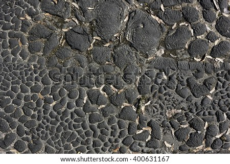 Spotty texture of a convex old dry bituminous surface - stock photo