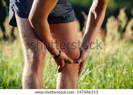 Sprained knee injury. Runner touching his leg. - stock photo