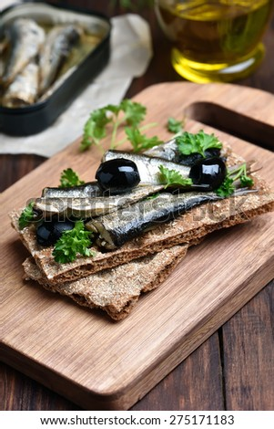 Sprats, herbs and olives on bread over wooden cutting board - stock photo