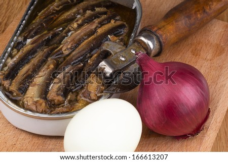 sprats in a tin with red onion, boiled egg and opener - stock photo