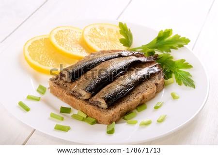 Sprats sandwiches on white plate - stock photo