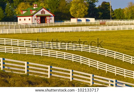 Sprawling acres of fenced in green pastures surround a horse farm ranch in Kentucky, USA - stock photo