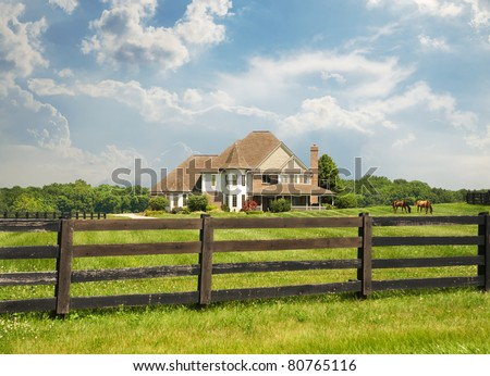 Sprawling green pastures and a wood fence surround a horse farm in Kentucky, USA. - stock photo