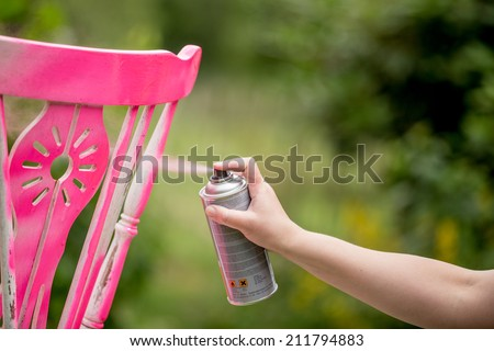 Spray paint an old chair pink - stock photo