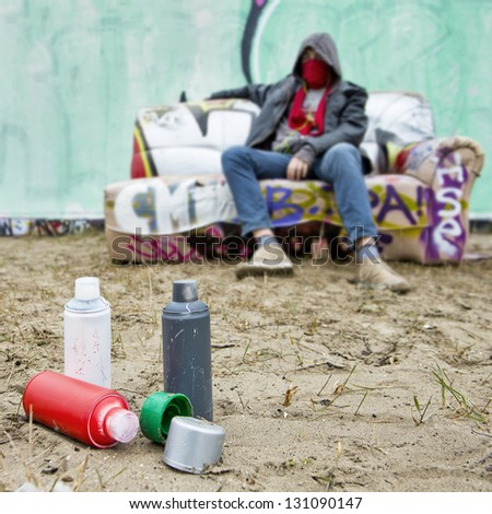 Spray paint cans on the sand in front of a large spray painted graffiti wall, with an artist, posing on a tagged couch, out of focus - stock photo