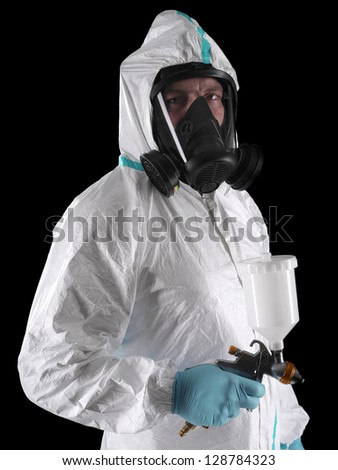 Spray painter wearing white coverall, respirator and spray gun shot over black background - stock photo
