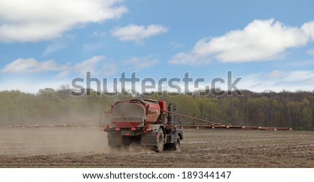 Spray truck applying chemicals to a farm field - stock photo
