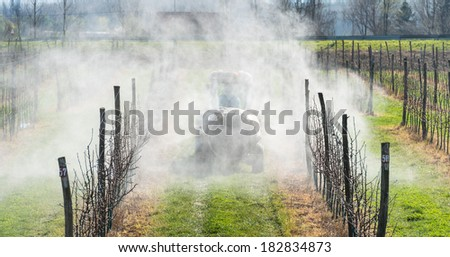 spraying apple orchard in spring - stock photo