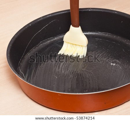 Spreading butter on a cake container - stock photo