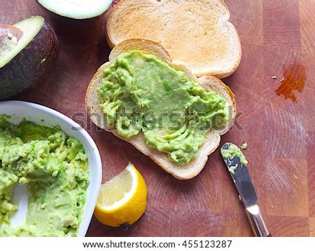 Spreading mashed avocado on toast slices - stock photo