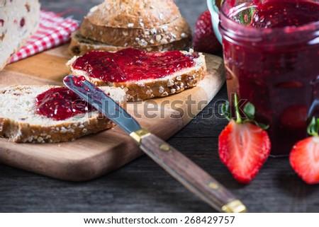 spreading strawberry jam on bread - stock photo