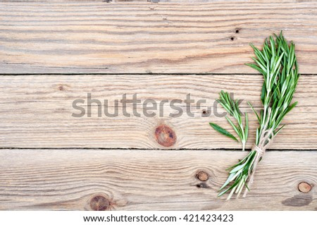 Sprigs of rosemary on old rustic wooden background with copy space. Herbs for cooking. Top view - stock photo