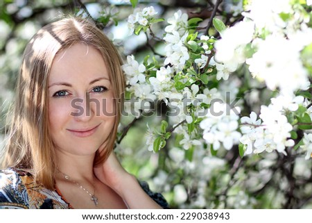 Spring beauty girl with long blonde hair outdoors. Blooming trees. Romantic young woman portrait - stock photo