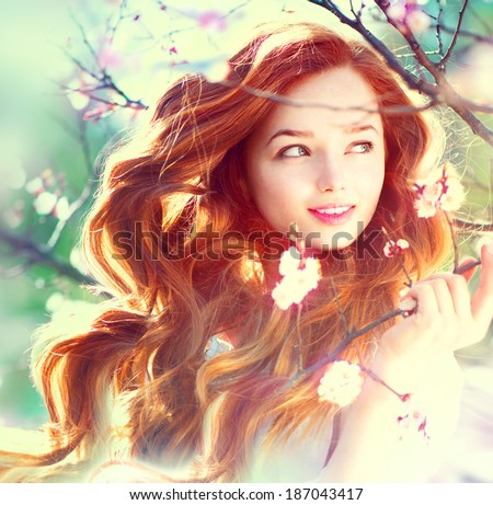 Spring beauty girl with long red blowing hair outdoors. Blooming trees. Romantic young woman portrait. Nature - stock photo