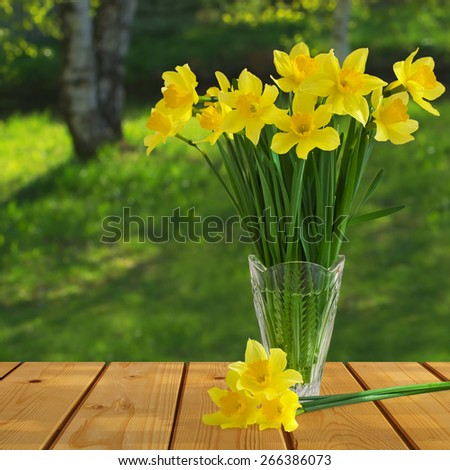 Spring bouquet of yellow daffodils in a glass vase on the table of the old wooden boards with blurred natural background - stock photo