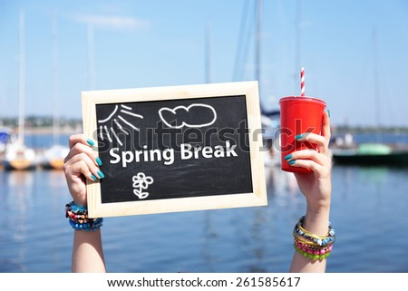 Spring break concept. Chalkboard in female hands on beach background - stock photo